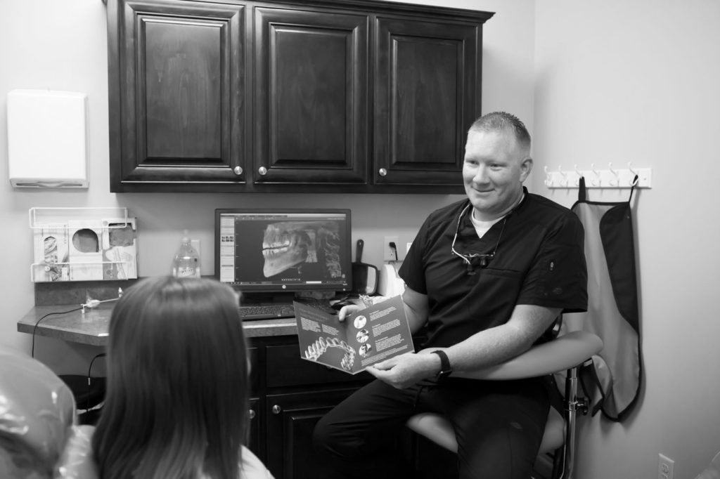 dentist holding a cosmetic dentistry booklet open while talking to a dental patient