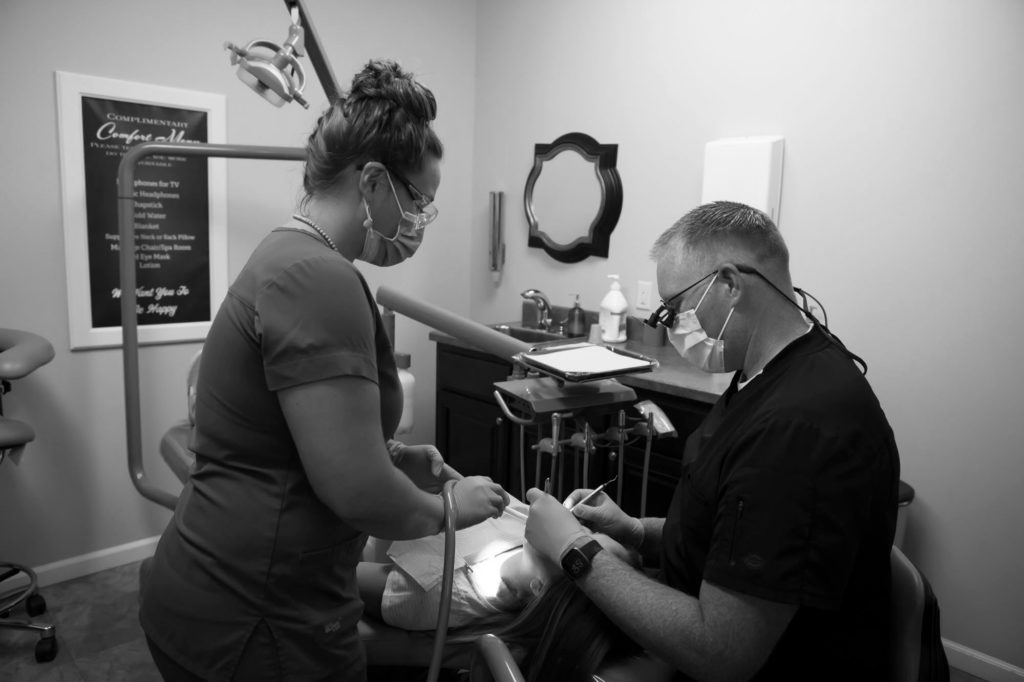 dentist examining a patient's teeth while a dental assistant helps