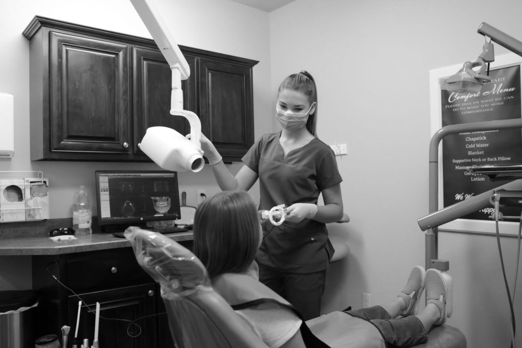 dental assistant talking to a patient in dental chair before taking a dental xray